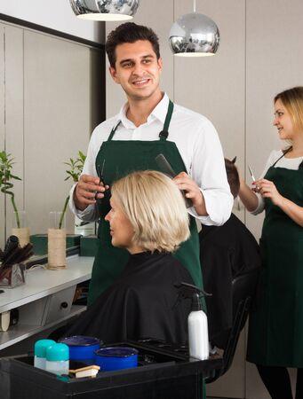 hair stylist: Professional stylist cutting hair of elderly blonde in hair salon