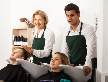 19's: Two professionals hairdressers working with hair of clients in washing tray at the hairdresser