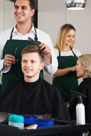 18's: Positive male hairstyler serving teenager in hair of salon Stock Photo