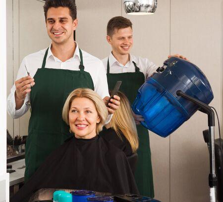 hair stylist: stylist cutting hair of elderly blonde Woman hairdresser in salon