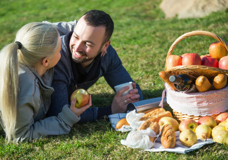 sandwitch: Young lovely couple chatting as having picnic in sunny day