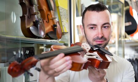 selecting: Male musician selecting classical violin in music instruments shop