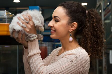russian hamster: Smiling female holding cute decorative rabbit in petstore