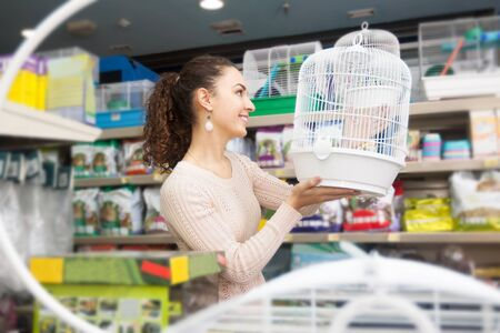russian hamster: Average female customer choosing cage for hamster in shop Stock Photo
