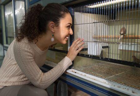 petshop: Portrait of happy girl watching singing birds in petshop