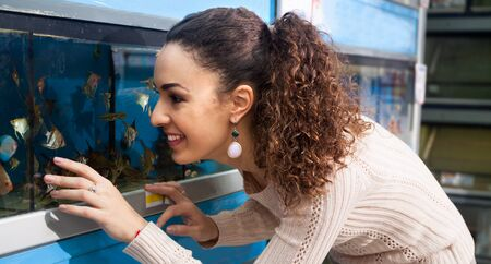 petshop: Portrait of young female watching tropical fish in petshop Stock Photo