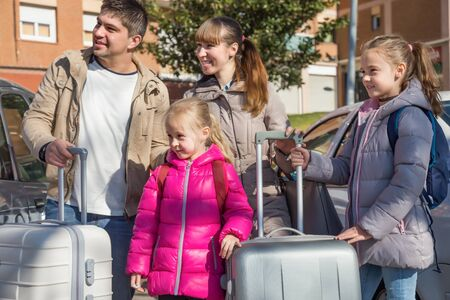 4s: Parents with two amazing daughters with suitcases in journey Stock Photo