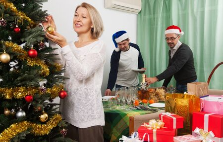 decorating christmas tree: people decorating Christmas tree in home interior Stock Photo