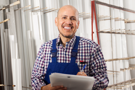 erector: smiling Male surveyor in coverall doing inspection and checking papers Stock Photo