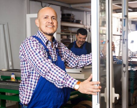 plastic made: The worker is proud of the door made of plastic