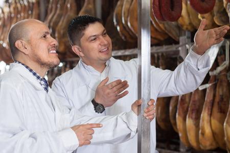 carniceria: tecnólogos de carnicería en blanco articulaciones de cheques vestido de jamón ibérico en la fábrica
