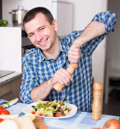 english ethnicity: smiling man adding spice to the salad