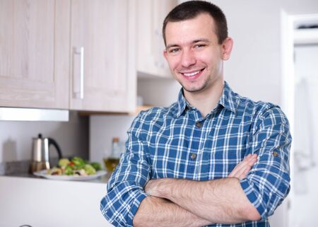 25s: Pretty young man posing in the kitchen and smiling
