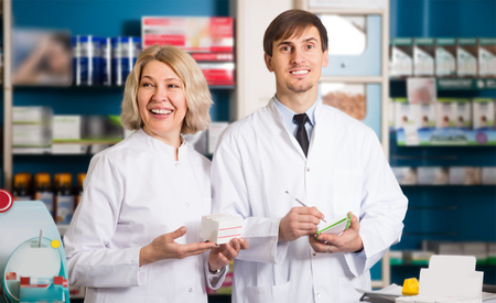 farmacy: Portrait of two smiling pharmacists working in modern farmacy Stock Photo