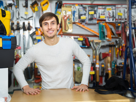 tooling: Positive young male seller posing at tooling section of household store Stock Photo