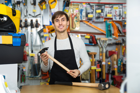 tooling: Ordinary male seller posing at tooling section of household shop