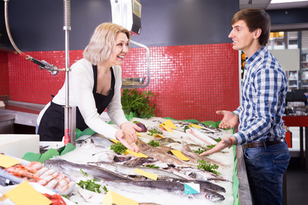 fish selling: Mature woman selling fish to male customer in store Stock Photo