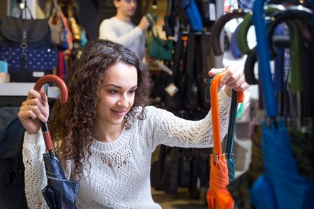 haberdashery: Young woman purchasing automatic umbrella in haberdashery store