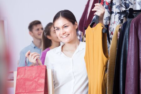 chose: Happy young woman in a clothing store chose a dress Stock Photo