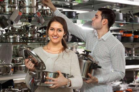 utensilios de cocina: par de la familia la elecci�n de las cacerolas en la tienda de utensilios de cocina