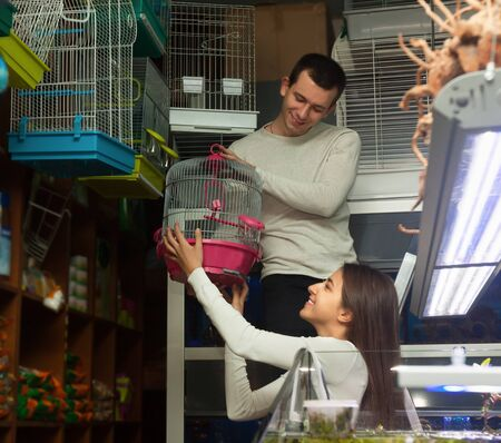 19's: Young boyfriend helping girl to choose rainforest cage in zoo shop