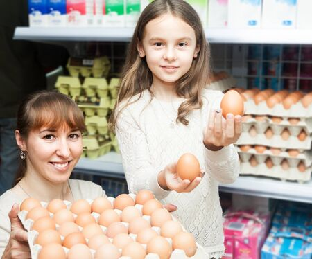 choosing selecting: Woman with curious little daughter choosing selecting eggs at dairy store Stock Photo