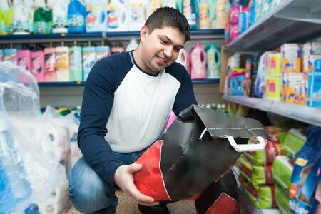 Ordinary middle class smiling guy purchasing coal at supermarket