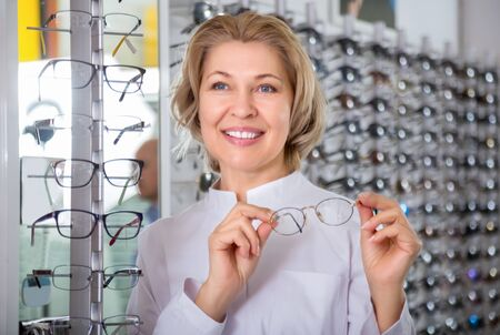 Eldery professional smiling female ophthalmologist in optics store Stock Photo