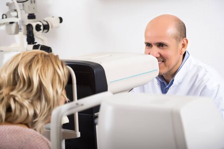Elderly ophthalmologist and female pensioner checking eyesight in clinic