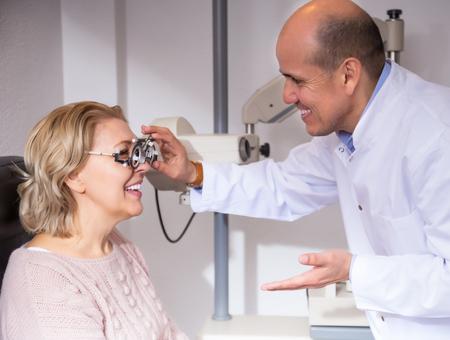 Elderly male optician examinating eyesight at the female pensioner