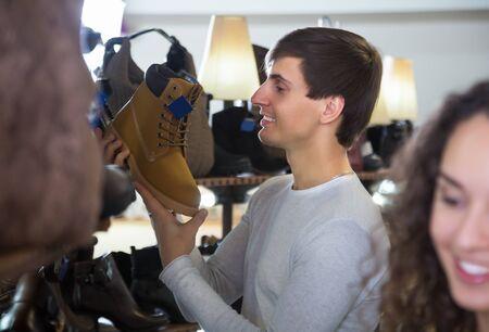 buying shoes: Hombre que compra zapatos de invierno en una tienda de zapatos