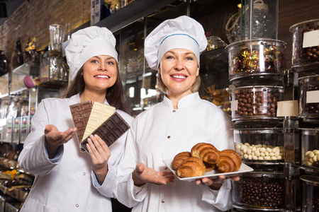 saleswomen: Smiling saleswomen selling fine chocolates and sweet pastry in coffee house