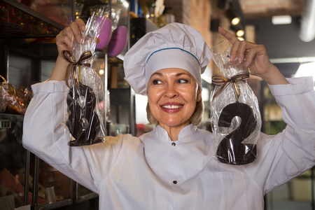 mature shopwoman posing with fine chocolate numbers and cakes for sale Stock Photo