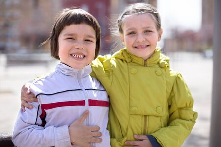 two children posing outdoors in the spring. focus on boy