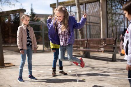 children games. blonde Girl jumps over the rope in the yard in spring Stock Photo