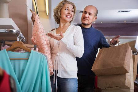 gladful: Man and woman buys some clothess  at shop