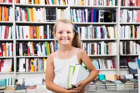 Prodigy: happy child girl chose a lot of books in the library