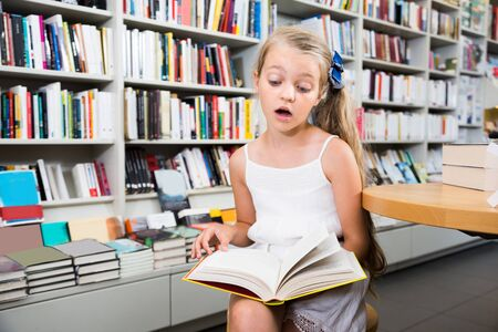 ittle: lsurprised ittle smart girl reading a book in the school library Stock Photo