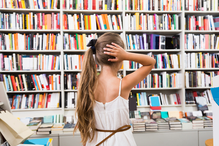 Prodigy: blonde smart girl child bemused a lot of books in a bookstore Zdjęcie Seryjne