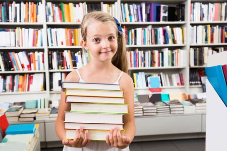 Prodigy: smiling child girl chose a lot of books in the library