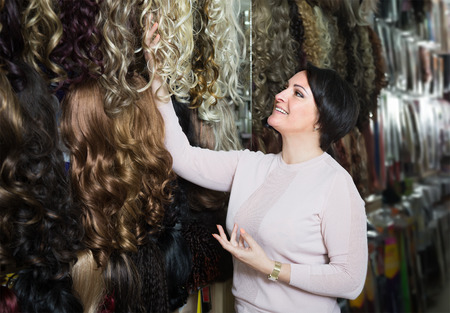 peruke: smiling middle aged brunette woman stylish wig in store
