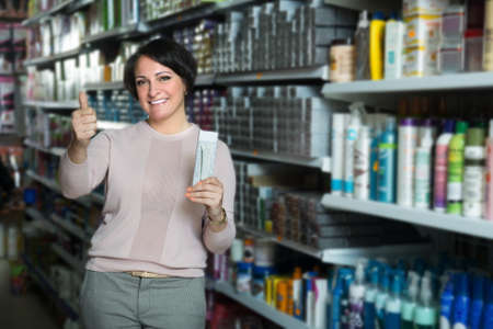 beauty shop: Elegant female customer buying hair care products in beauty shop and smiling Stock Photo