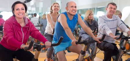 satisfied older men and women are engaged in the gym. focus on male in the centre
