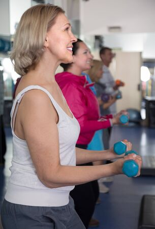 german ethnicity: positive mature blonde woman doing exercises with dumbbells in the gym Stock Photo