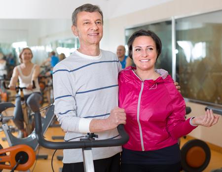 diligent: pareja madura diligente presenta en la gimnasia