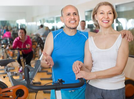 active adult community: Portrait of positive mature couple in sportswear in gym