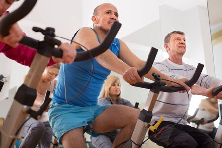 active adult community: mature males on exercise bikes in the gym Stock Photo