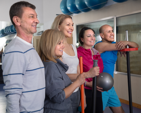 active adult community: Portrait of group of aged men and women in top form in modern gym. focus on woman in the centre