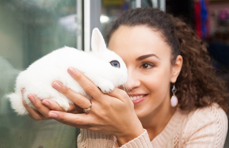 petshop: Ordinary female customer watching Blanc de Hotot rabbit in petshop  focus on the rabbit Stock Photo