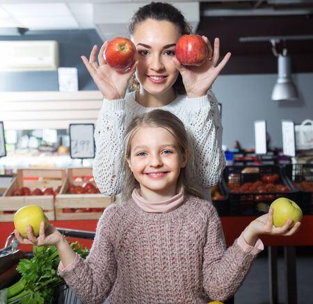 english ethnicity: Brunette female with a smiling little girl considering apples at store